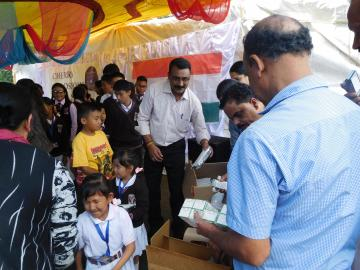 MEMBERS OF THE KERALA CLUB GIVING AWAY SNACKS AND STATIONARY ITEMS